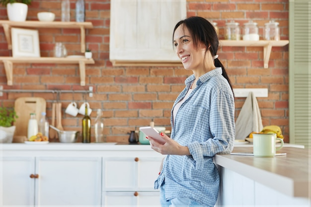 Heerlijke lachende brunette schattige vrouw draagt huiskleding, staat in de buurt van de keukentafel