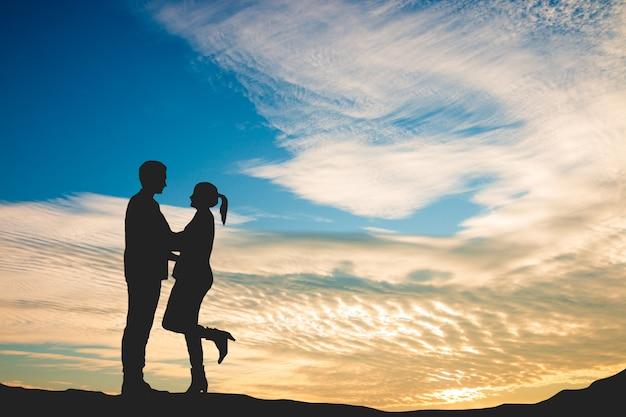 Heerlijke liefhebbers in de prachtige zonsonderganghemel, liefde op valentijnsdag
