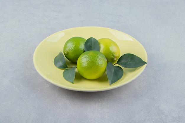 Heerlijke limoenvruchten met bladeren op gele plaat.