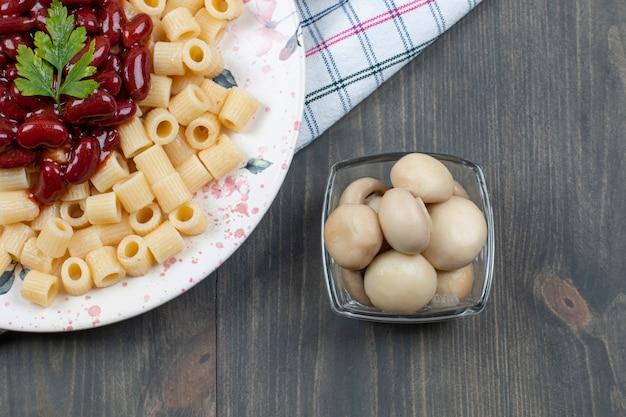 Heerlijke macaroni met bonen en peper op een houten tafel