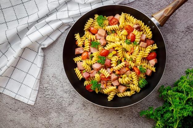 Heerlijke macaroni met groenten en gesneden ham. bovenaanzicht.