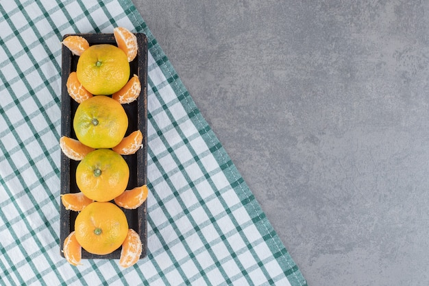 Heerlijke mandarijnen en segmenten op zwarte plaat. hoge kwaliteit foto
