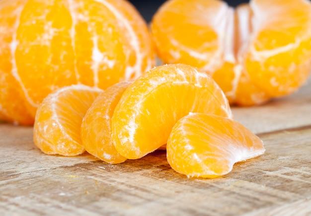 Heerlijke mandarijnen, gepelde sinaasappelschil liggend op een houten tafel, gezonde citrusvruchten met veel vitamines
