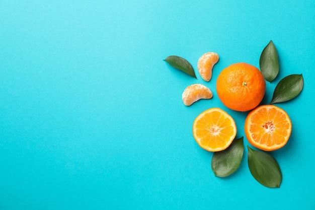 Heerlijke mandarijnen op turkooizen achtergrond, ruimte voor tekst