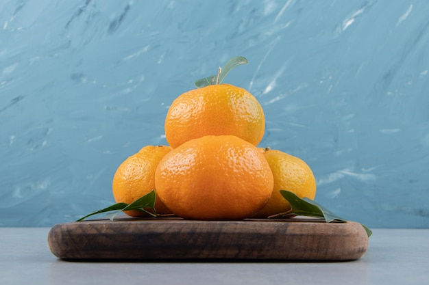 Heerlijke mandarijnvruchten op een houten bord.