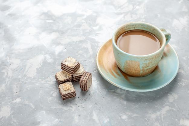 Heerlijke melkkoffie met chocoladewafels op licht bureau, de zoete suiker van het chocoladekoekje