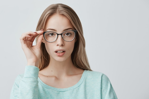 Heerlijke mooie blonde vrouw in trendy bril, draagt lichtblauwe trui, staat binnenshuis