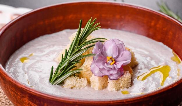 Heerlijke mooie champignonsoep in een bruin bord met een houten lepel op een donkerbruin oppervlak