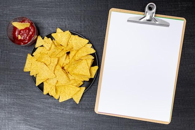 Heerlijke nacho's met dip naast klembord