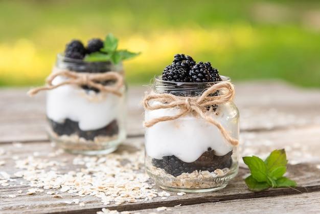 Heerlijke natuuryoghurt met bramen en muntblaadjes. op frisse lucht. tegen een achtergrond van groen in glazen potten.