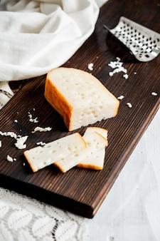 Heerlijke nederlandse goudse kaas met kaasblokken op een oude houten witte tafel.