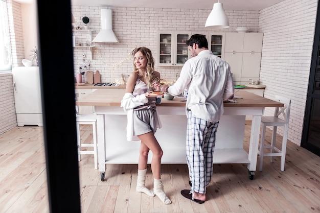 Heerlijke ochtend. vrij langharige jonge vrouw in een satijnen top en haar man voelt zich goed tijdens het ontbijt samen