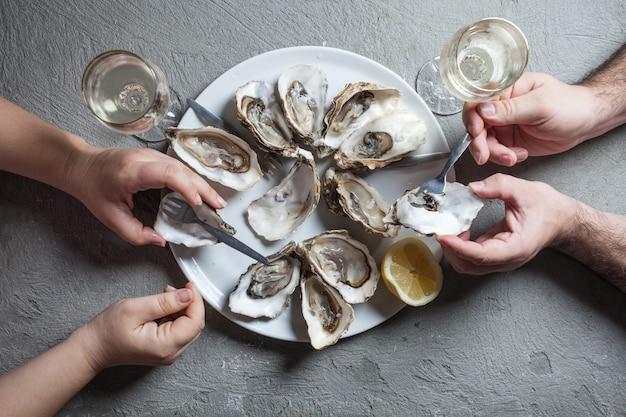 Heerlijke oesters met schijfje citroen en glazen witte wijn, bovenaanzicht