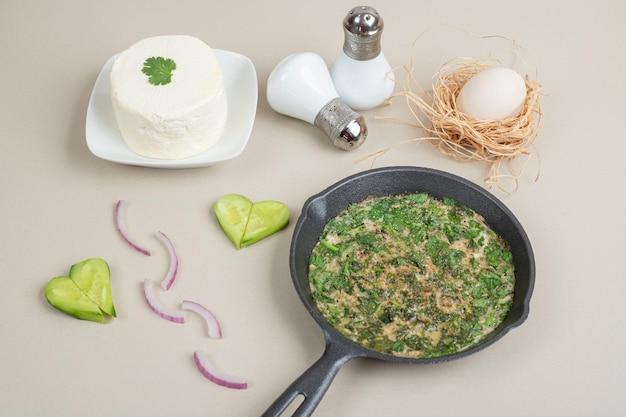 Heerlijke omelet met greens op donkere pan.