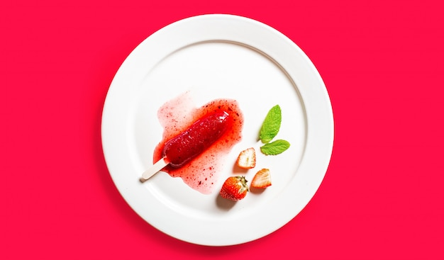 Heerlijke ontdooide aardbeien ijslollys op witte ronde schotel op rode achtergrond