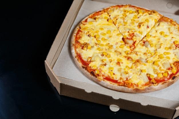 Heerlijke oven gebakken pizzeria schotel met mozzarella, parmezaan en kaas, geleverd in een kartonnen doos