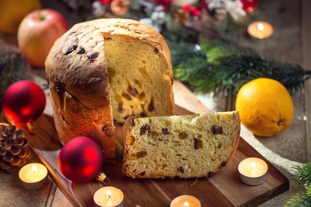 Heerlijke panettone op kersttafel met versieringen en adventskrans en kaarsen.
