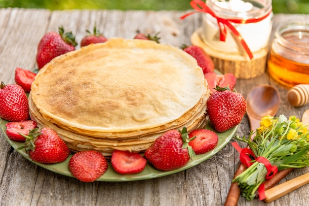 Heerlijke pannenkoeken met aardbeien en honing als ontbijt.
