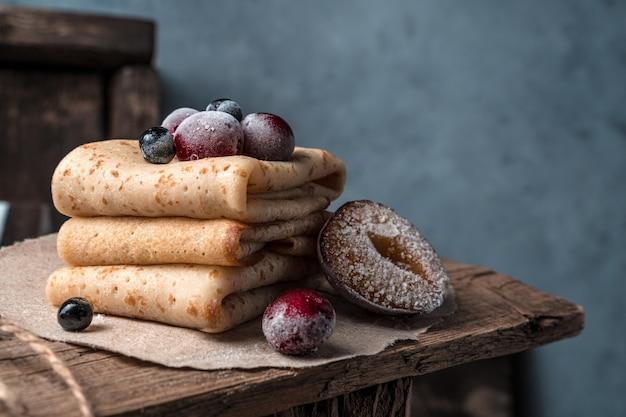 Heerlijke pannenkoeken met bevroren kersen, pruimen en lijsterbes op een houten dienblad.