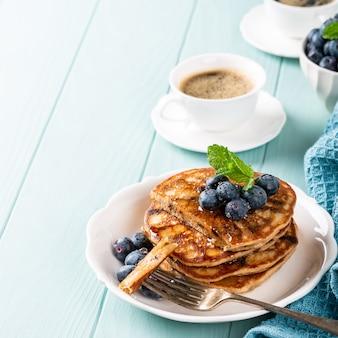 Heerlijke pannenkoeken met chocoladedruppels, honing en bosbessen. gezond ontbijtconcept met exemplaarruimte
