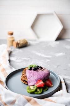Heerlijke pannenkoeken met helften van aardbei en kiwi hoge weergave