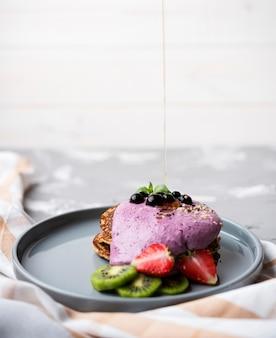 Heerlijke pannenkoeken met helften van aardbei en kiwi op plaat
