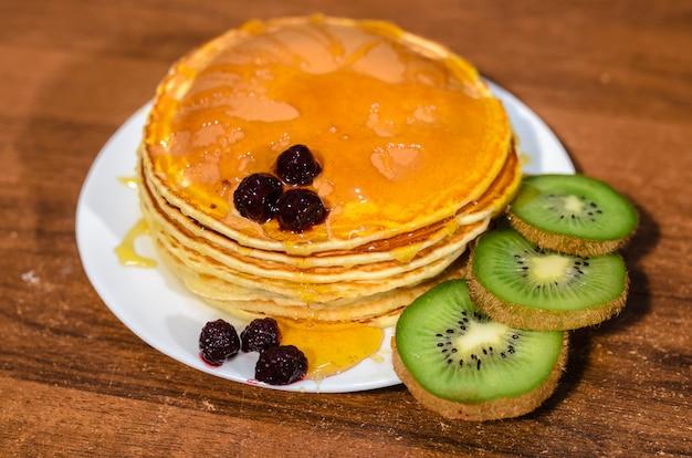 Heerlijke pannenkoeken met honing, kiwi en bessen.