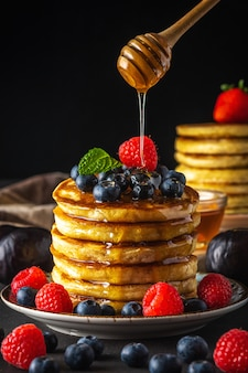 Heerlijke pannenkoeken met verse bessen en druipende honing op donkere achtergrond. voedsel concept.