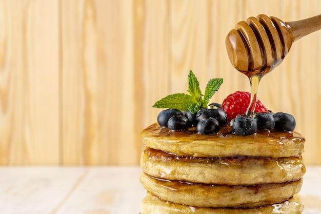 Heerlijke pannenkoeken met verse bessen en druipende honing op houten achtergrond. voedsel concept.