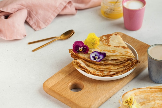 Heerlijke pannenkoeken op borden, versierd met bloemen en koffiemokken