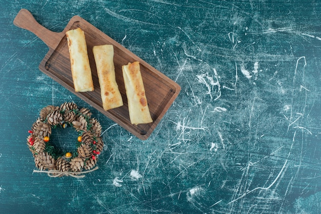 Heerlijke pannenkoeken op een klein dienblad naast een dennenappelkrans op blauw.