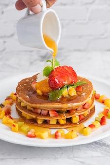 Heerlijke pannenkoeken op marmeren tafel met fruit