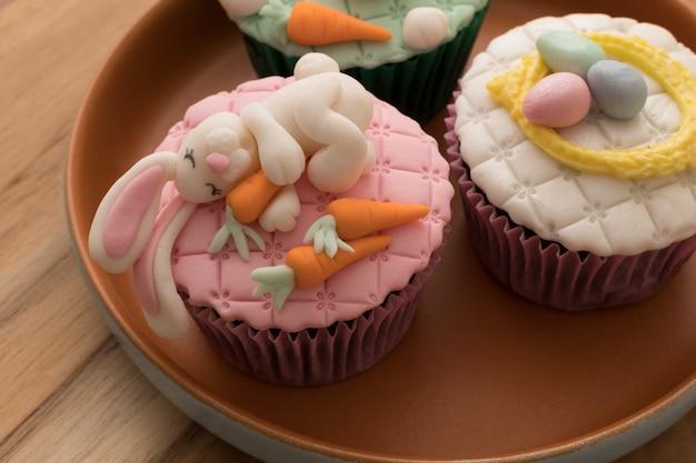 Heerlijke pasen cupcakes op rustieke plaat en houten achtergrond
