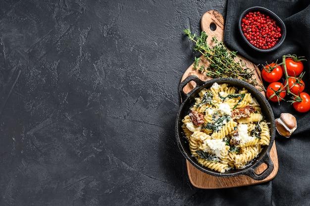 Heerlijke pasta fusilli schotel met romige spinaziesaus en gedroogde tomaten. zwarte achtergrond. bovenaanzicht.