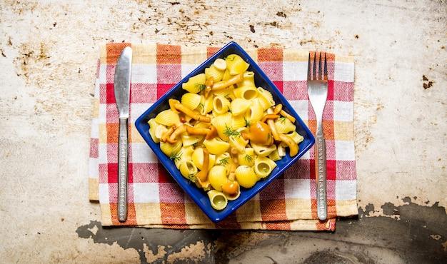 Heerlijke pasta met champignons op een bord op de stof. op rustieke achtergrond. bovenaanzicht