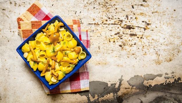 Heerlijke pasta met champignons op een bord op de stof. op rustieke achtergrond. vrije ruimte voor tekst. bovenaanzicht