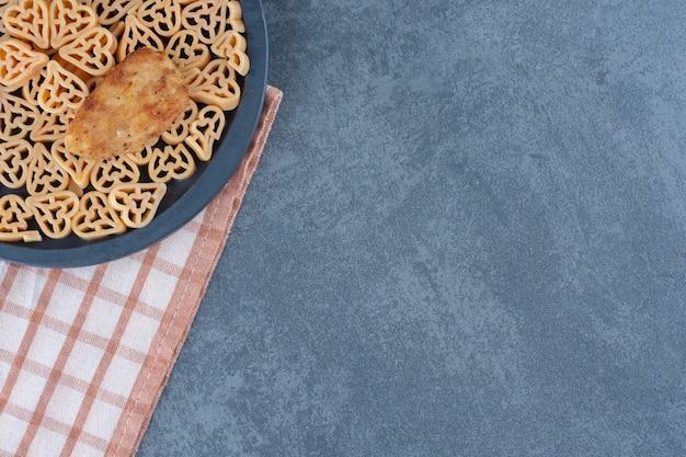 Heerlijke pasta met goudklompjes op zwart bord.