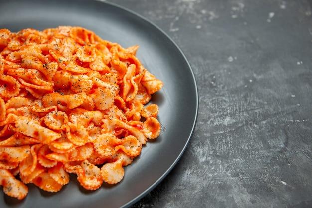 Heerlijke pastamaaltijd op een zwarte plaat voor het diner op donkere achtergrond