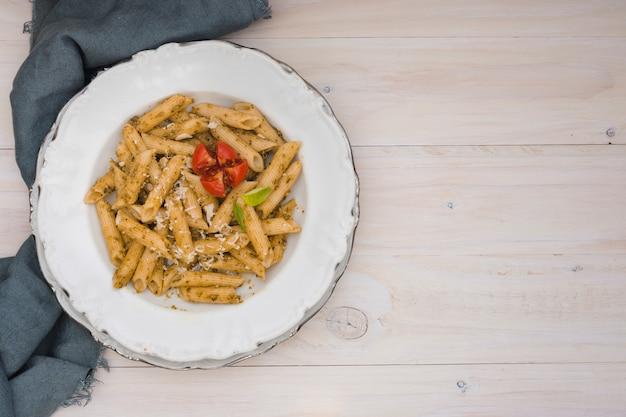 Heerlijke pennedeegwaren met geraspte kaas en tomaat op ceramische witte plaat op houten bureau