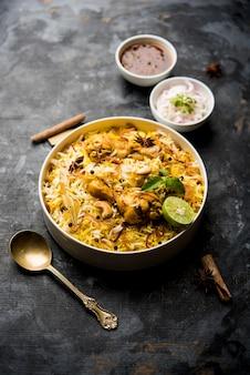 Heerlijke pittige kippenbiryani in kom over humeurige achtergrond, het is een populair indiaas en pakistaans eten Premium Foto