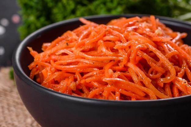Heerlijke pittige sappige heldere koreaanse wortelen in keramische gerechten op een donkere betonnen achtergrond. aziatische keuken