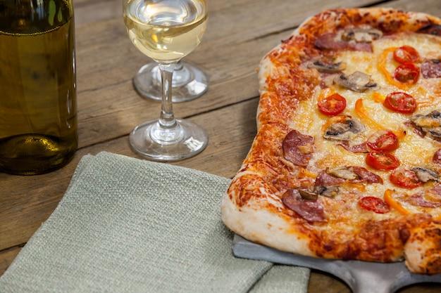 Heerlijke pizza geserveerd op pizzaplaat met een glazen fles wijn en wijn