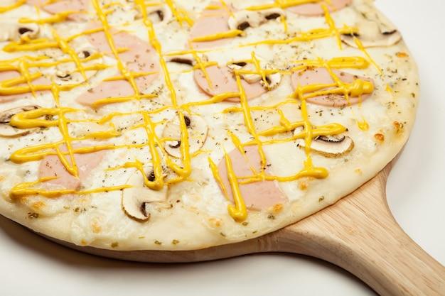 Heerlijke pizza ham champignons geserveerd op een houten plaat, ingrediënten