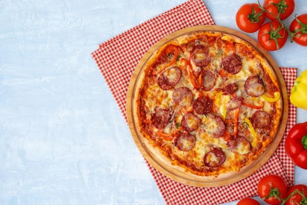 Heerlijke pizza met worstjes op grijs