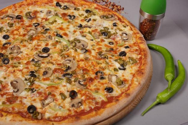 Heerlijke pizza mexicana met tomatensaus champignons en jalapeno pepers met kruiden