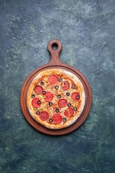 Heerlijke pizza op houten snijplank op donkerblauw oppervlak met vrije ruimte