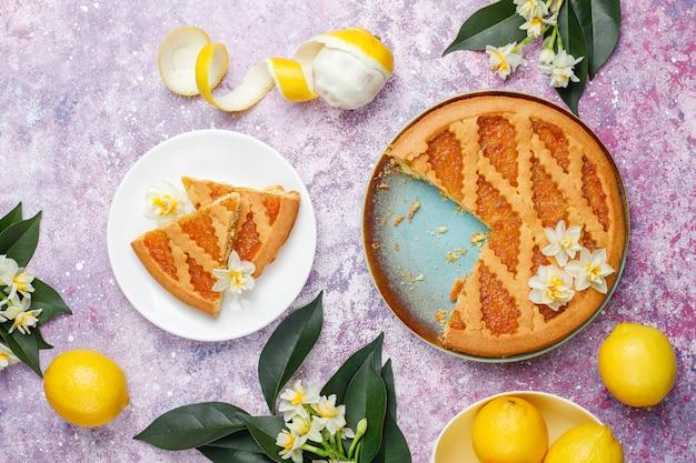 Heerlijke plakjes citroentaart met verse citroenen en een kopje thee, bovenaanzicht