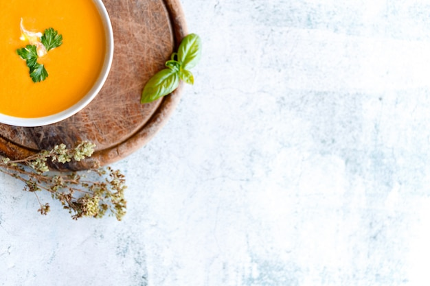 Heerlijke pompoensoep in kom op marmeren tafel