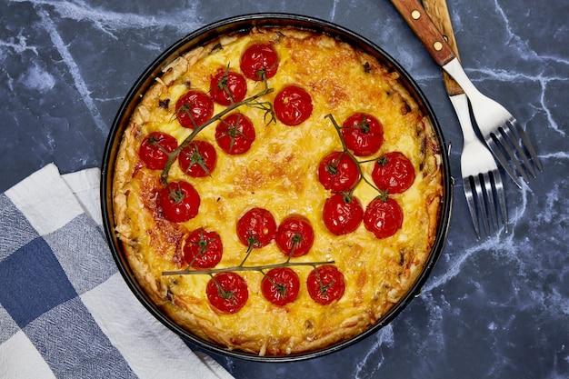 Heerlijke quiche met gebakken tomaten op tak en kip, gevuld met room, kaas en eieren.