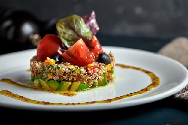 Heerlijke quinoasalade met avocado en tomaten op zwarte achtergrond.